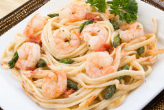 Shrimp Scampi with Asparagus. Shrimp scampi made with linguini, asparagus, diced tomatoes, butter, garlic, herbs and parsley. Served on stacked plates. Shot in Royalty Free Stock Photos