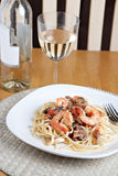 Shrimp Scampi Dish. A delicious shrimp scampi pasta dish with mushrooms and diced tomatoes along with a glass of pinot grigio white wine Royalty Free Stock Photography
