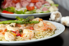 Shrimp Scampi Dish. A delicious shrimp scampi pasta dish with antipasto salad in the background Royalty Free Stock Photos