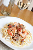 Shrimp Scampi with Linguine. A delicious shrimp scampi over linguine dish along with a glass of pinot grigio white wine Royalty Free Stock Image