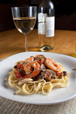 Shrimp Scampi with Linguine. A delicious shrimp scampi over linguine dish along with a glass of pinot grigio white wine Royalty Free Stock Photos