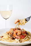 Shrimp Scampi with Pasta. A delicious shrimp scampi pasta dish along with a glass of pinot grigio white wine.  Shallow depth of field with focus on the fork Stock Image