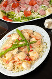 Shrimp Scampi with Pasta. A delicious shrimp scampi pasta dish with antipasto salad in the background Royalty Free Stock Photography