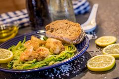 Shrimp Scampi served over zucchini noodles sauteed with lemon, garlic, butter and herbs. With blue accessories, wine and oil Royalty Free Stock Photography