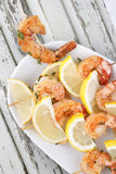 Shrimp Scampi Skeweres with Souce. Grilled shrimp scampi skewers on a plate with souce and lemon stock image
