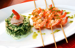 Shrimp skewers meal. Three shrimp skewers dish and savory green rice side with sauce Stock Image
