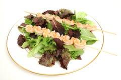 Shrimp skewers on salad on pla. Picture of shrimp skewers on salad on plate Royalty Free Stock Photography