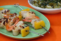 Shrimp, squid and yellow pepper skewers. On plate royalty free stock images