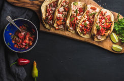 Shrimp tacos with homemade salsa, limes and parsley. On wooden board over dark background. Top view, copy space. Mexican cuisine Royalty Free Stock Images