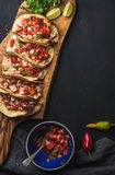 Shrimp tacos with homemade salsa, limes and parsley. On wooden board over dark background. Top view, copy space. Mexican cuisine Stock Image