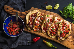 Shrimp tacos with homemade salsa, limes and parsley. On wooden board over dark background. Top view. Mexican cuisine Royalty Free Stock Photo