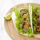 Shrimp tacos on round bamboo board on white wooden background, side view. Mexican food. Closeup stock images
