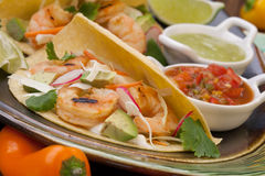 Shrimp Tacos. Two shrimp tacos with salsa, guacamole, beer, garnished with mini bell pepper and lime stock photography