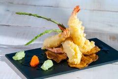 Shrimp tempura. Close up of shrimp tempura appetiser served on black tile Stock Images