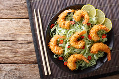 Shrimp tempura with green pasta and sesame close-up on a plate. Horizontal view from above stock images