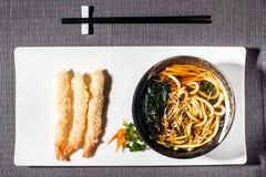 Shrimp tempura served with udon, carrots, soya sprouts and mixed algae in broth. Shrimp tempura served with consomme with udon, carrots, soya sprouts and mixed royalty free stock photography