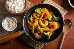 Shrimp Teriyaki with Broccoli and Sesame Seeds. A delicious shrimp teriyaki stir fry with broccoli and sesame seeds on a wooden table top stock image