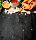 Shrimp with tomato sauce on the old fabric. Stock Photos