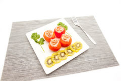 Shrimp with tomato. An white board with shrimp and tomato and to decorate some slices of kiwi fruit royalty free stock photos