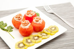 Shrimp with tomato. An white board with shrimp and tomato and to decorate some slices of kiwi fruit stock photo