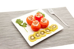 Shrimp with tomato. An white board with shrimp and tomato and to decorate some slices of kiwi fruit Royalty Free Stock Photography