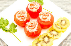 Shrimp with tomato. An white board with shrimp and tomato and to decorate some slices of kiwi fruit stock photos