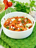 Shrimp and tomatoes with feta in white bowl on green napkin Royalty Free Stock Image