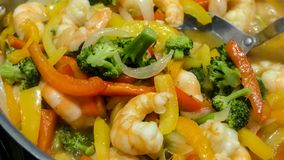Shrimp and Vegetable Stir Fry. Home cooked shrimp and vegetable stir fry with a cooking spoon in a wok for frying stock photography