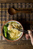 Shrimp wonton noodle soup with choy sum. Closeup of a young man getting some noodles with his chopsticks from an earthenware bowl with shrimp wonton noodle soup Stock Images