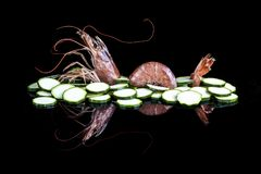 Shrimp and zucchini on a black reflective surface stock images