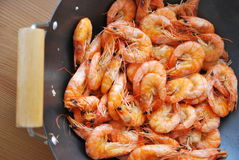 Shrimps. In wok on a wooden table, ready to serve Stock Images