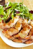 Shrimps baked in bacon, with salad Royalty Free Stock Photography