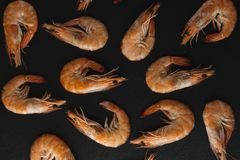 Shrimps on black background. Delicious seafood appetizer served boiled or grilled with spices. Close up. Top view Stock Photo