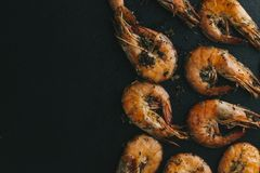 Shrimps on black background. Delicious seafood appetizer served boiled or grilled with spices. Close up. Top view Royalty Free Stock Photography