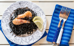 Shrimps with black seaweed and slices of lemon stock image