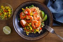 Shrimps with cauliflower, mango avocado, red paprika pepper and lime. Overhead, horizontal royalty free stock photo