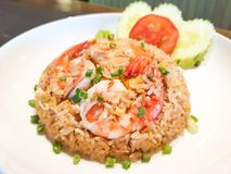 Shrimps fat fried rice garnish with slice cucumbers and tomato on top with shrimps. Slice green leeks and parsley royalty free stock image