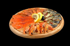 Shrimps and a fish. Seafoods on a wooden dish on a black background Stock Photo