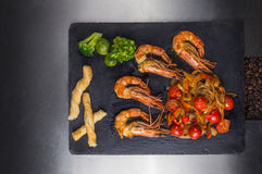 Shrimps with fresh and fried vegetables on dark background. On silver background Royalty Free Stock Image