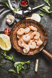 Shrimps in fried pan on rustic kitchen table background with cooking ingredients Royalty Free Stock Photo
