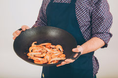 Shrimps in the fry pan. Hand holding stir fried shrimp head pan Stock Photo
