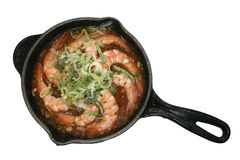 Shrimps on a frying pan about a leek. Royal shrimps in onions sauce Royalty Free Stock Images