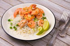 Shrimps with ginger rice and green peas, lime on white plate on wooden background. royalty free stock images