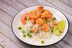 Shrimps with ginger rice and green peas, lime on white plate on wooden background. Shrimps with ginger rice and green peas, lime on white plate on wooden royalty free stock photo