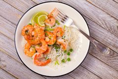 Shrimps with ginger rice and green peas, lime on white plate on wooden background. royalty free stock photography
