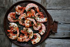 Shrimps on the grill with vintage wooden background Stock Photo