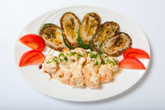 Shrimps and grilled zucchini on a white plate Stock Images