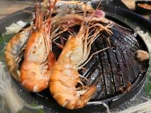 Shrimps grilling on hot pot. stock images
