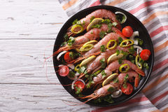Shrimps with herbs and vegetables in a pan. horizontal top view Royalty Free Stock Photo