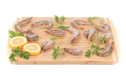 Shrimps and lemon slices on cutting board. Stock Photos